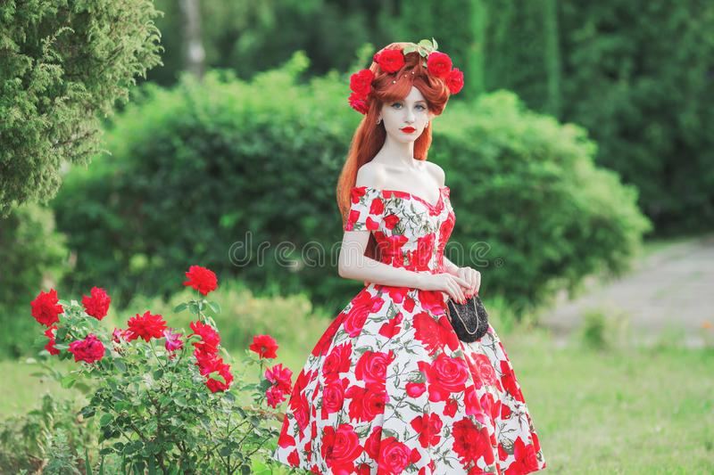 Valentine Day background. Girl with red lips in stylish dress with print of roses on beautiful summer background. Beauty redhead stock images