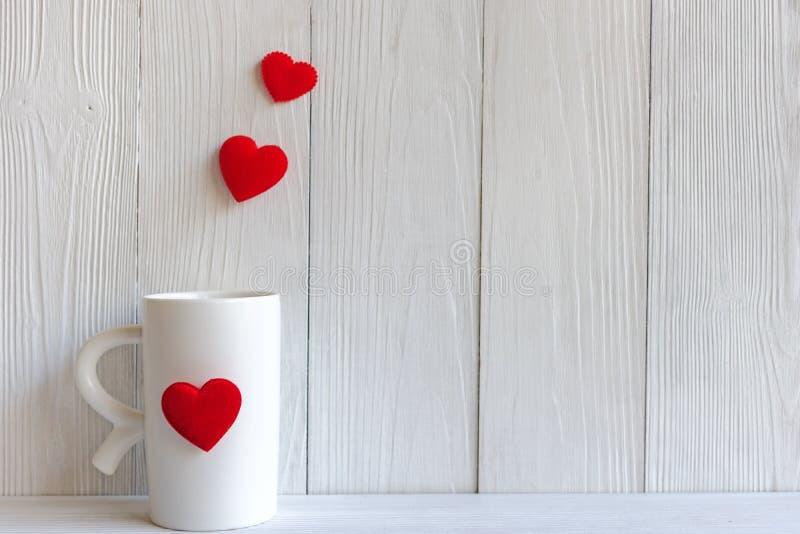 Valentine Day com café vermelho do copo costurou corações do descanso enfileira a beira, fundo branco de madeira fotografia de stock royalty free