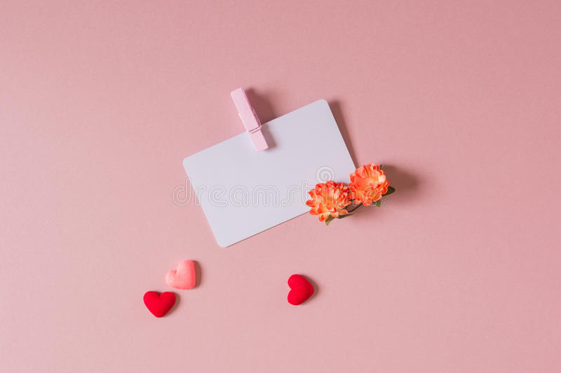 Valentine day composition. Credit / visiting card template with clamp, spring flowers, and small hearts on light pink background. Top view stock photo
