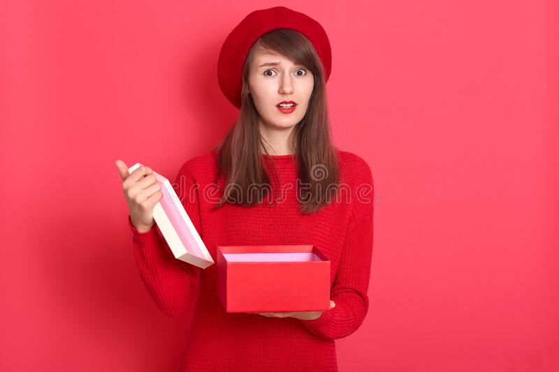 Valentine day concept. Sad woman opening empty box gift present. Elegant attractive model wearing red sweater and beret, looking royalty free stock photo