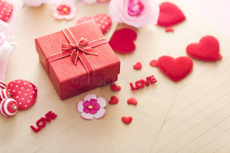 Valentine Day gåvaask med röda hjärtor och rosor på bokstavskuvert royaltyfri fotografi