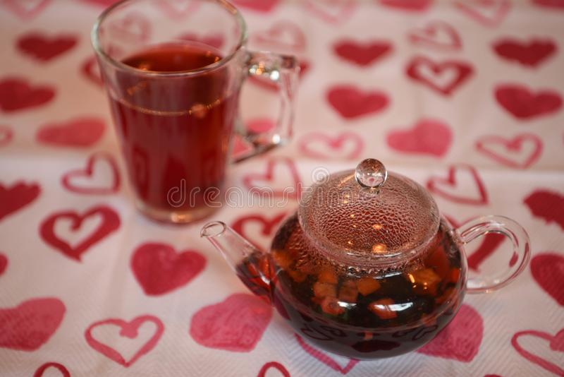 Valentines day drink photography image of a glass teapot and cup filled with hot apple spice flavor tea on love heart cloth stock image