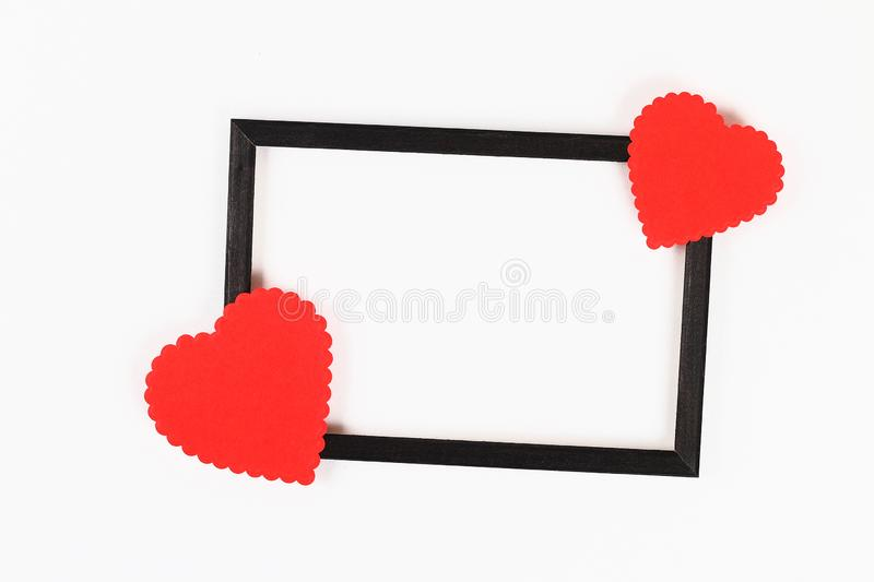 Valentine day layout. Black frame with red curly hearts on a white background. St. Valentines Day, day love, February 14 concept. Copy space, top view, flat stock image