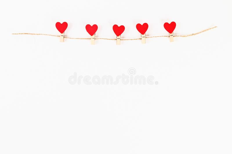 Valentine day layout. Red hearts on wooden clothespins on a jute twine on a white background. St. Valentines Day, day love, stock photo