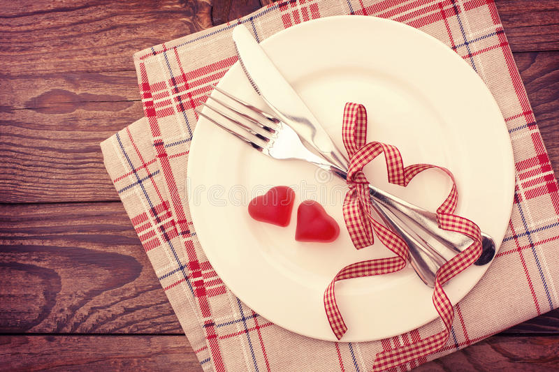 Valentine day love beautiful. Romantic dinner. Tableware and hearts on wooden background royalty free stock photography