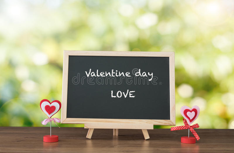 Valentine day and LOVE text on black board and wood table top wi stock image