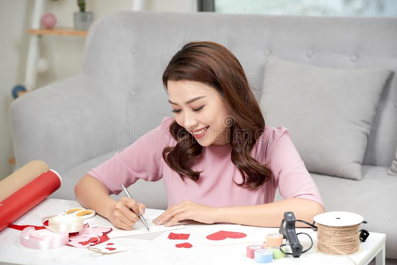 Valentine day theme. Beautiful romantic woman making present for her couple.  royalty free stock image