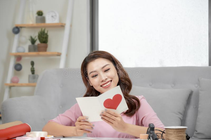 Valentine day theme. Beautiful romantic woman making present for her couple.  royalty free stock images