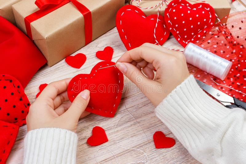 Valentine day theme. Workplace for preparing handmade decorations. Top view of female hands sew felt heart. Packed gifts, tools sh royalty free stock photo