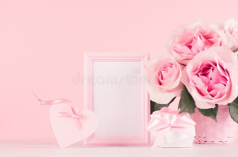 Valentine days decor and gift in soft light pastel pink color - romance bouquet of roses, heart, gift box, blank frame on wood. royalty free stock photos