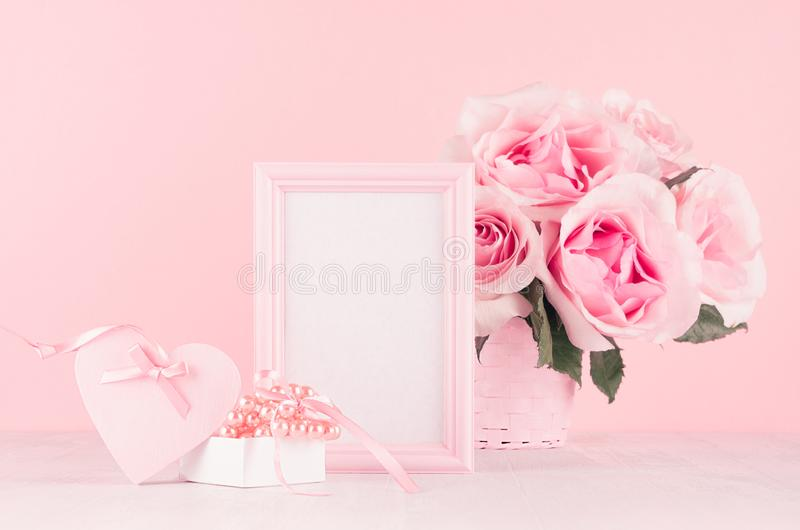 Valentine days decor for home in soft pastel pink - romance bouquet of roses, heart, gift box with perls, ribbon and blank frame. royalty free stock photography