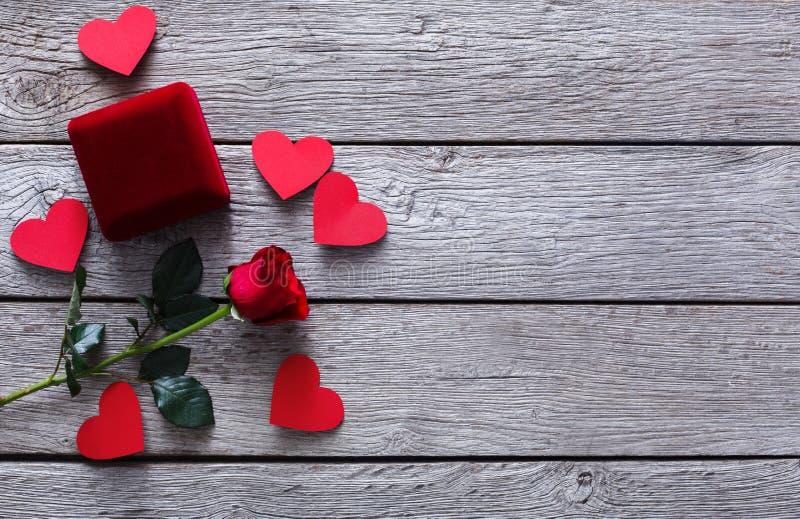 Valentine-de dagachtergrond, juwelendoos en nam bloem op hout toe stock afbeeldingen