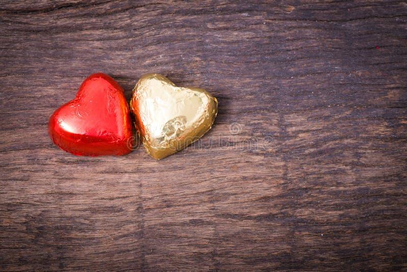 Valentine-decoratie, paarhart gestalte gegeven chocolade, rood en goud stock foto