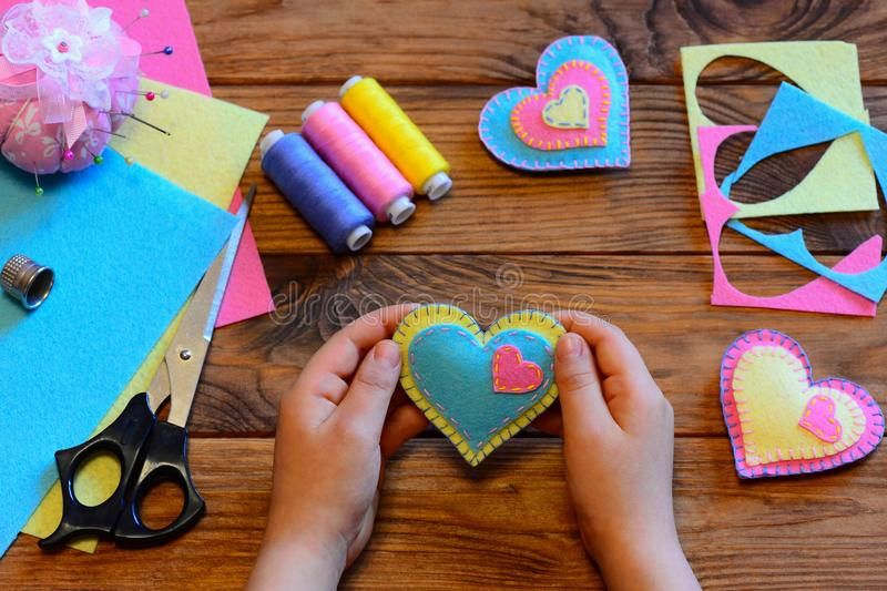 Child holds a felt valentine in his hands. Child made valentines from felt. Valentines day crafts idea. Felt heart ornaments. Valentine decorations idea royalty free stock photography