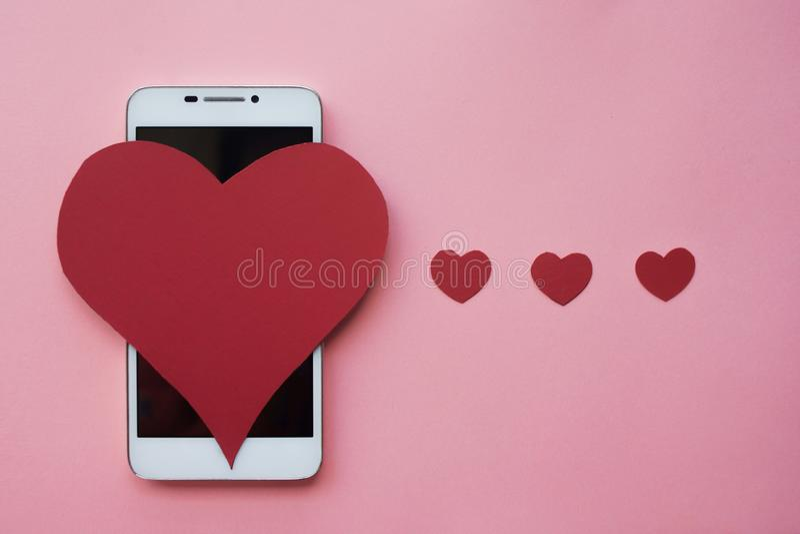 Valentine en smartphone Het concept aan gelijkaardig in sociale netwerken of het Dateren van app Roze achtergrond stock fotografie