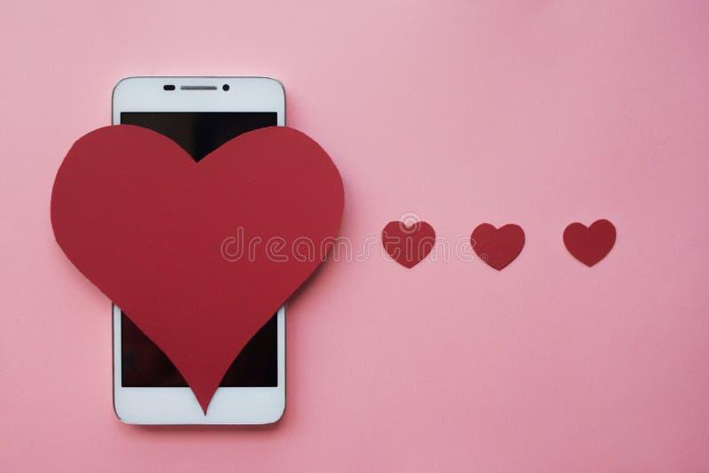 Valentine et smartphone Le concept à aimer dans les réseaux ou l'APP sociaux de dater Fond rose photographie stock