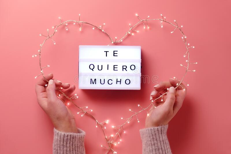 Valentine flat lay, top view on pink background. Lightbox with text. `Te quiero mucho` means `I love you` in Spanish. Light garland in heart shape held in royalty free stock photos
