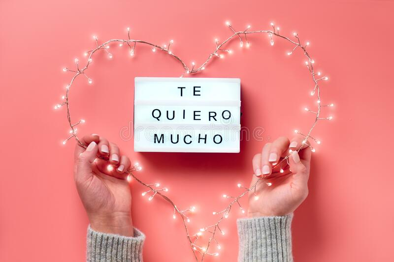 Valentine flat lay, top view on pink background. Lightbox with text. `Te quiero mucho` means `I love you` in Spanish. Light garland in heart shape held in stock photography