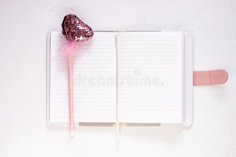 Valentine flatlay. Blank diary, pink heartshaped pen feathers on white background. Notebook mockup, cute girlish style. Valentine flatlay. Blank diary, pink royalty free stock photos