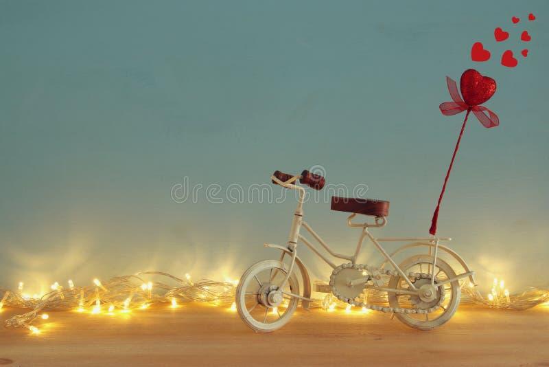 Valentine& x27; fundo romântico do dia de s com o brinquedo branco da bicicleta do vintage e coração vermelho do brilho nele sobr imagem de stock royalty free