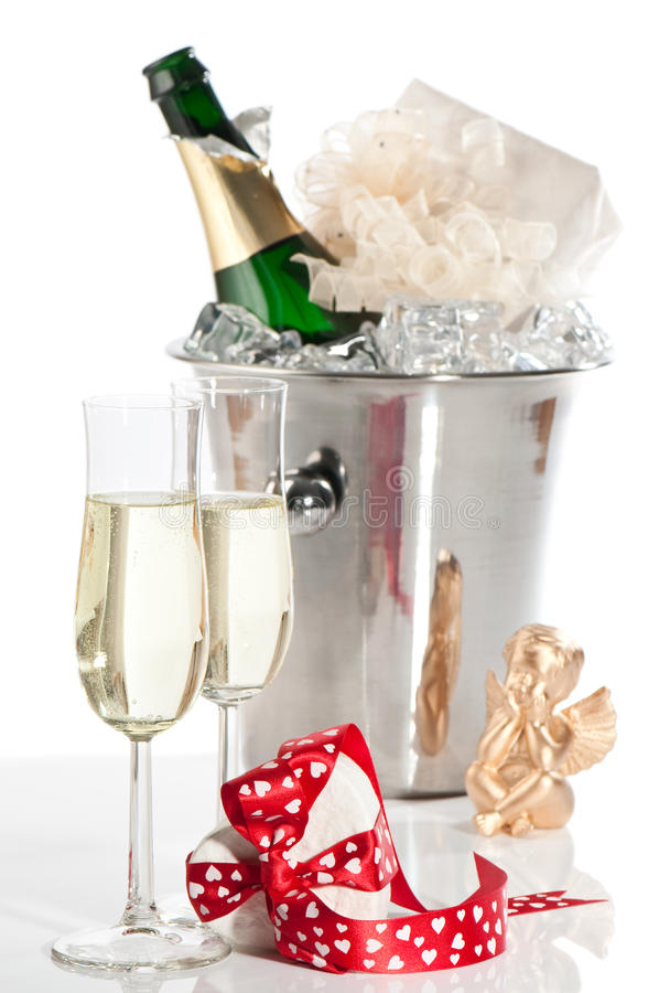 Valentine Gift. Valentine champagne with gift wrapped with heart bow, cherub and ice bucket in background stock photo