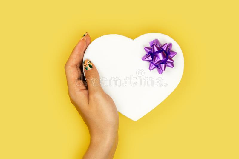 Valentine gift. Beauty Woman hands holding Gift box with purple bow over pastel yellow background. stock photos