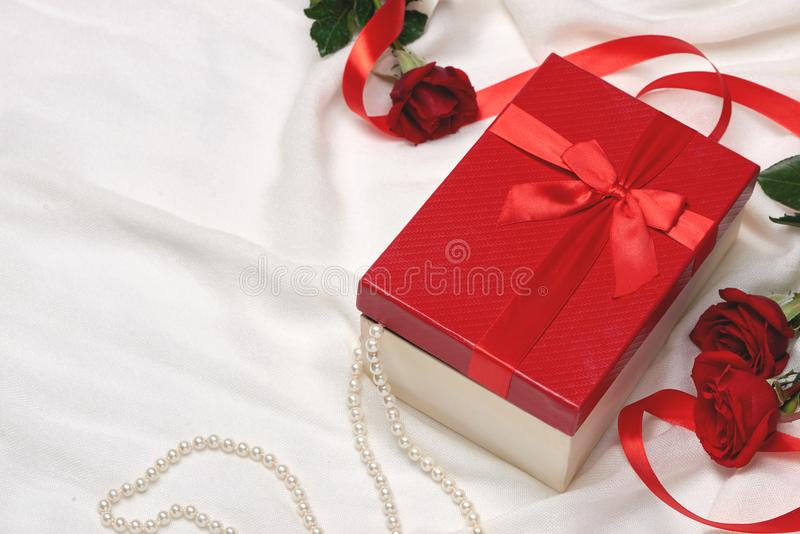 Valentine gift box. Red ribbon bow present with red roses on holiday royalty free stock photography