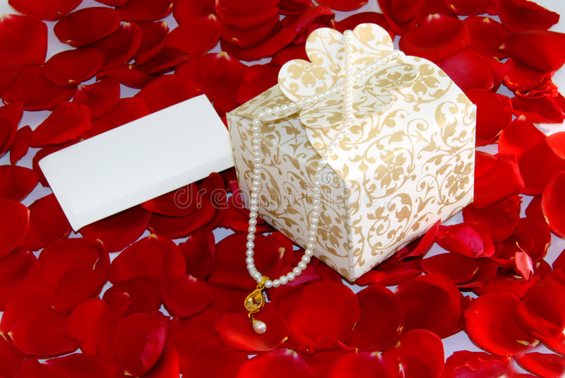 Valentine gift pearl on Rose petals. White valentine pearl gift box on rose flower petals royalty free stock photo