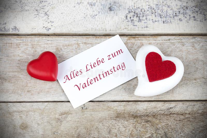 Valentine greeting card on wooden table with text Alles Liebe zum Valentinstag, written in German, which means Happy Valentine da stock photography