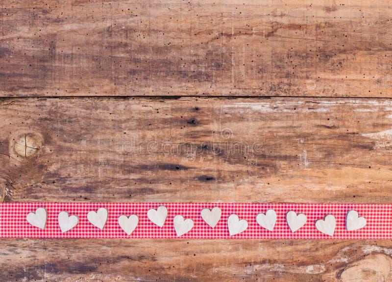 Valentine-hartendecoratie op rode lintgrens en rustieke houten achtergrond stock foto's