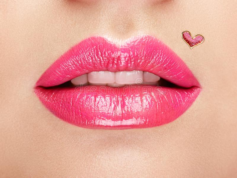 Lips painted with a lipstick heart. Valentine Heart Kiss on the Lips. Makeup. Beauty Lips with Heart Shape paint. Valentines Day. Beautiful Love Make-up royalty free stock images