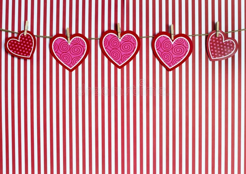 Valentine Hearts Hanging From Twine en un fondo rayado rojo imágenes de archivo libres de regalías