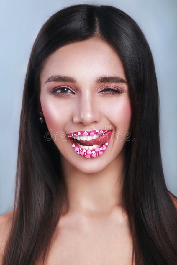 Valentine Hearts sweet makeup. Valentine`s Day make-up lips with pink hearts sugar sprinkles. Kiss on the Lips stock photo