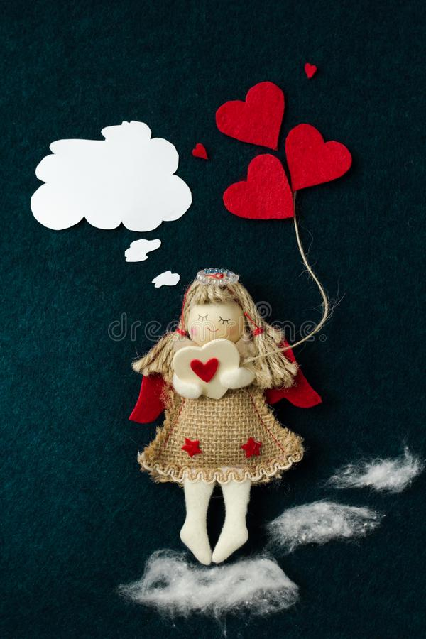 Valentine homemade with an angel from a fabric that bears hearts and dreams of a beloved on a dark background stock image