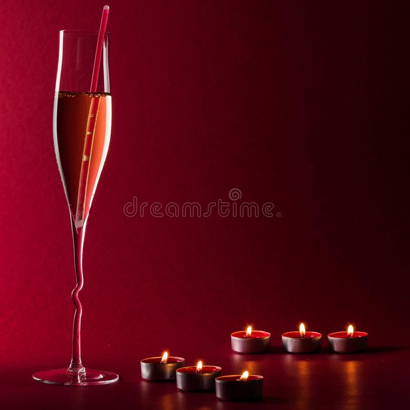 Valentine mood with a glass of champage, candles and a drinking straw on a red background. royalty free stock images