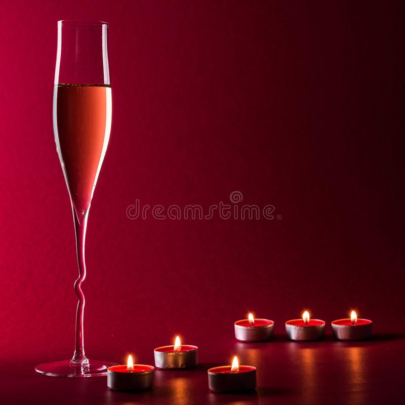 Valentine mood with a glass of champage and candles on a red background with flame and fire. royalty free stock image