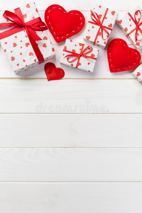 Valentine or other holiday handmade present in paper with red hearts and gifts box in holiday wrapper. Present box gift on white stock image