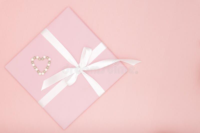 Valentine ou cadeau de rose de jour de femmes avec le ruban blanc d'arc décoré de petits coeurs sur le fond de papier de corail C images libres de droits