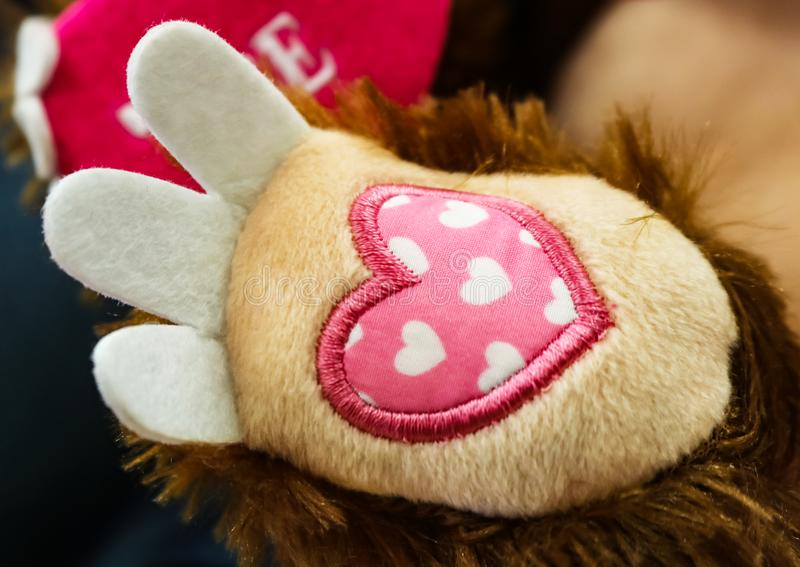 Valentine Paw - Pink fabric heart with embroidered on the foot of a stuffed toy with a stuffed heart that say LOVE in the backgrou stock photo