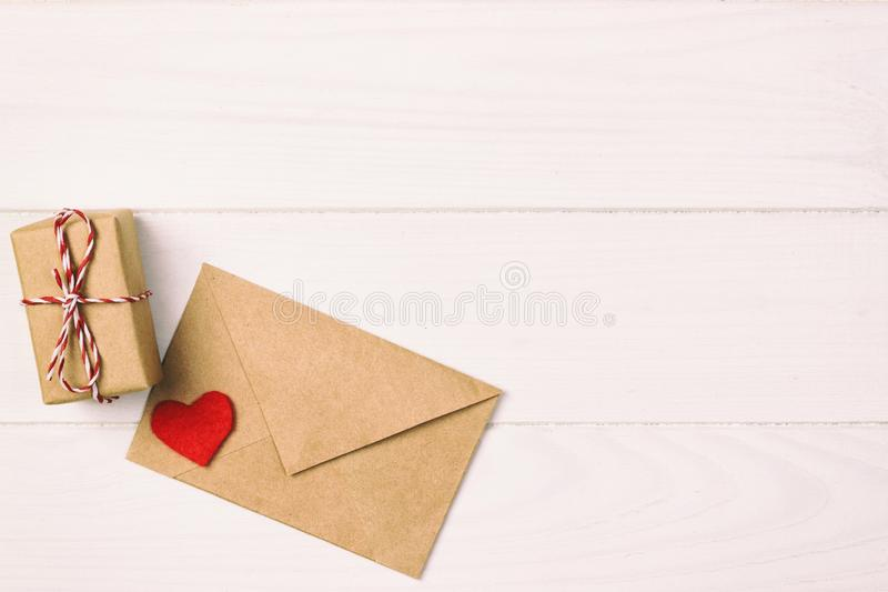 Valentine with red heart. A paper parcel wrapped tied toned, vintage. A red heart with gift box wrapped with paper kraft stock image
