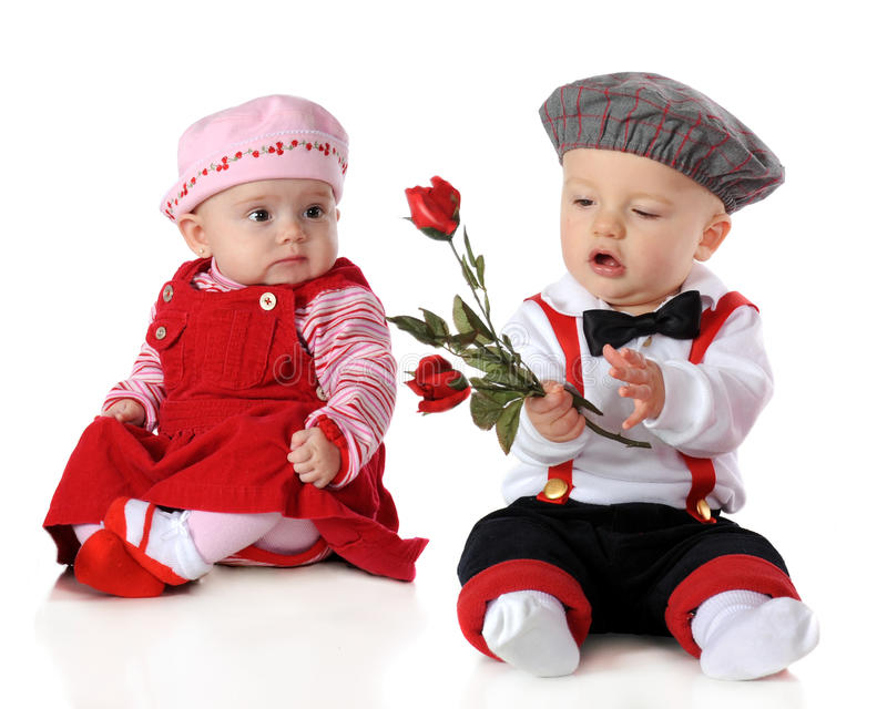 Valentine Roses for Me?. Babies dressed up for Valentine's Day. The boy holds long stemmed roses while the girl looks on royalty free stock photography