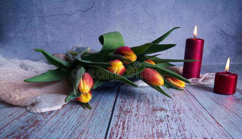 A beautiful bouquet of tulips and red candles. Valentine`s card: a beautiful bouquet of tulips and red candles stock photos
