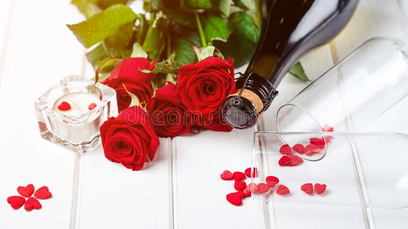 Valentine`s card. Beautiful romantic composition with red roses. Bottle of champagne and roses on white wooden table. Happy royalty free stock images
