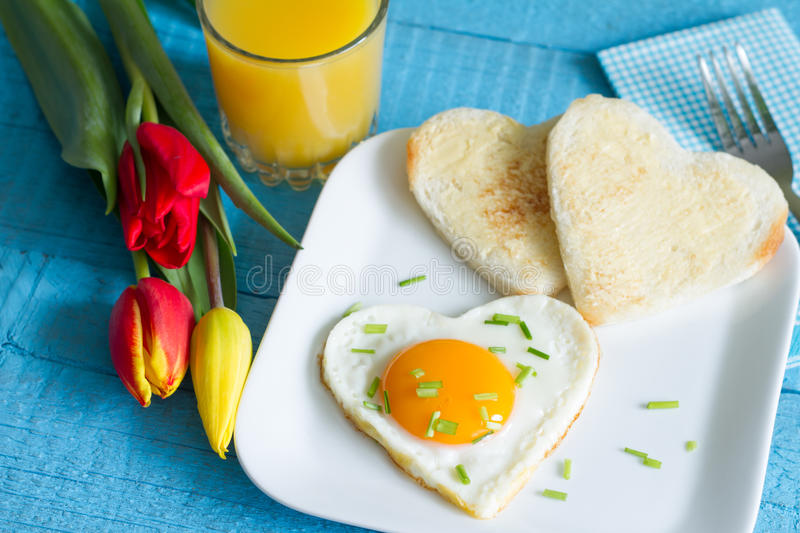 Valentine's Day abstract breakfast with egg heart and tulip stock photography