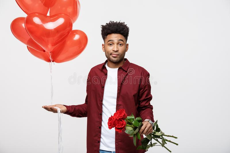 Valentine`s Day: African American man holding red rose and balloon with disappointed expression. royalty free stock photos