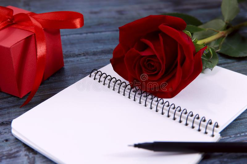 Valentine`s day background. On a blue wooden background an opened notebook, pen, gift and red rose. stock photography