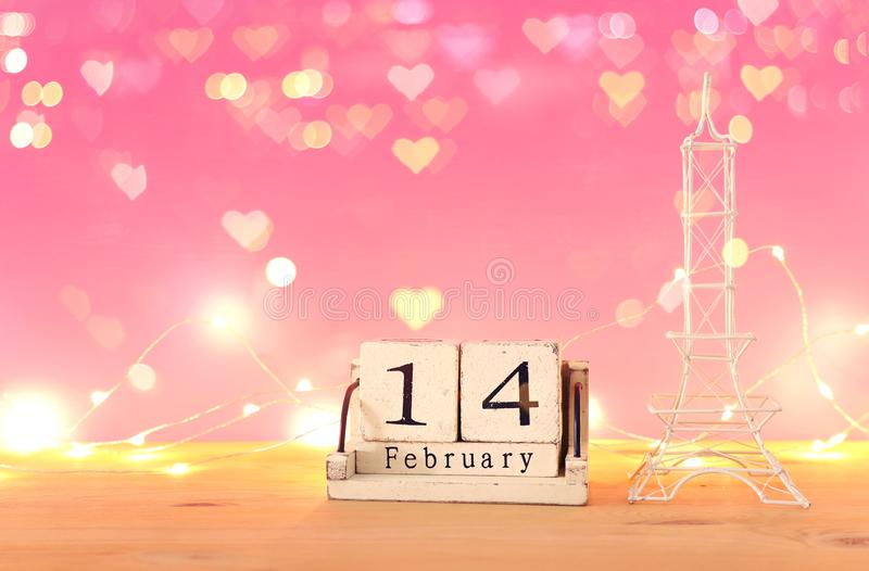 Valentine`s day background. Eiffel tower and vintage wooden calendar with 14th february date. Over table and pink bakground. Hearts overlay stock image