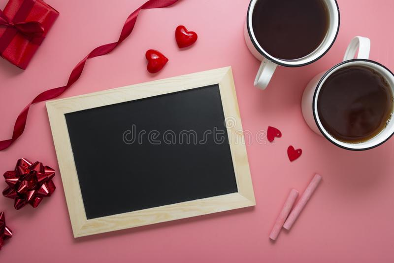 Valentine's day background. Flat lay chalk board frame, hearts andtwo cups, mock up with copy space. Love, gift box pink stock photos