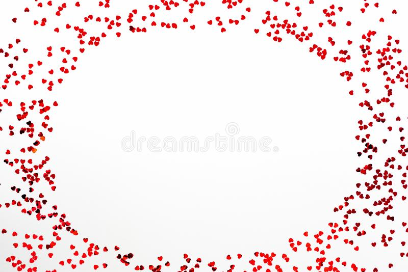 Valentine`s Day background - a frame of scattered heart shaped confetti over white background.  royalty free stock photos
