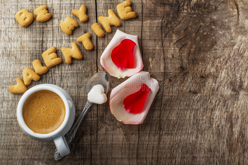 Valentine's Day background. Free space for a text. Valentine's Day background: Caption cookies in the form of letters and a cup of coffee with rose petals royalty free stock images